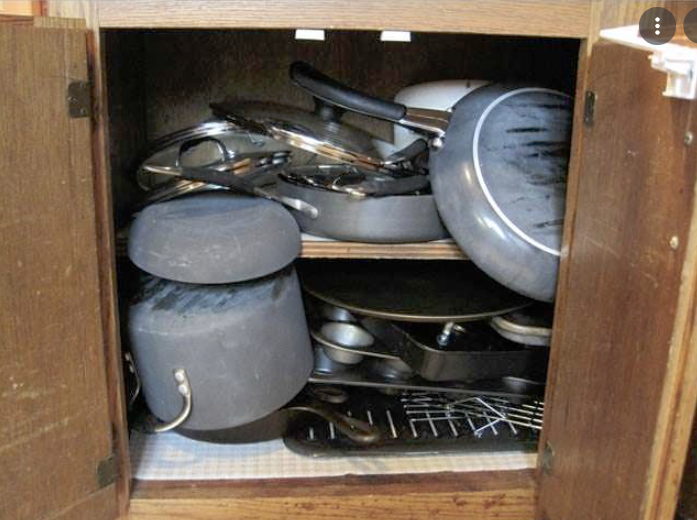 messy kitchen cabinet with pots on the top of each other